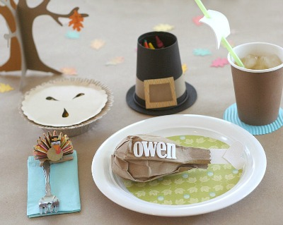 Cute table setting for kids Thanksgiving table. Pilgrim hat crayon holder, turkey leg placeholder, pretend pie, ship cup and turkey clip.